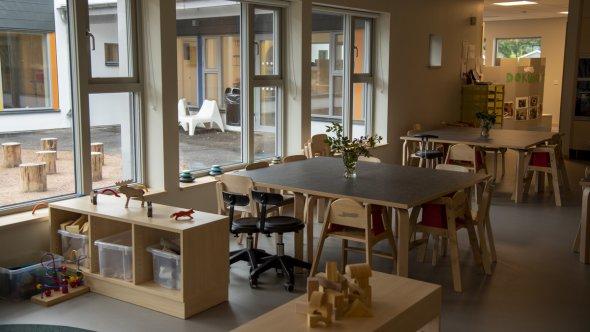 En bild på flera bord och stolar och en av en utegård som syns genom fönstret.