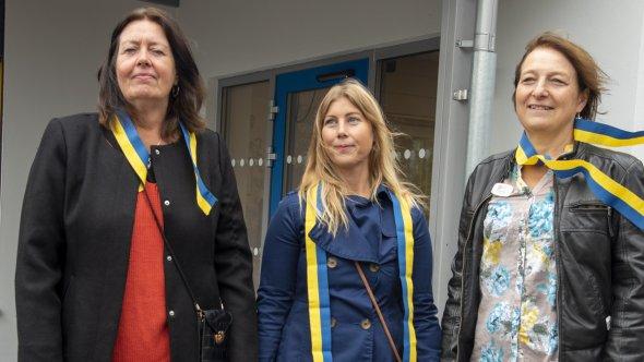 En bild på tre kvinnor med färgglada band runt halsen.