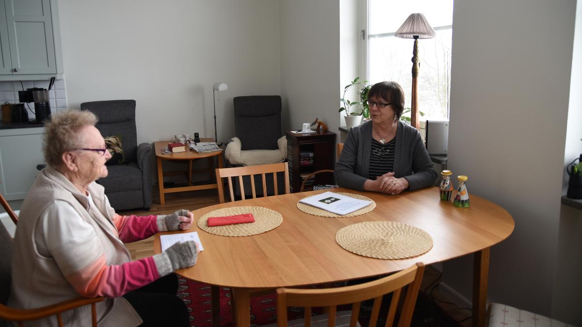Två kvinnor sitter och samtalar vid ett köksbord