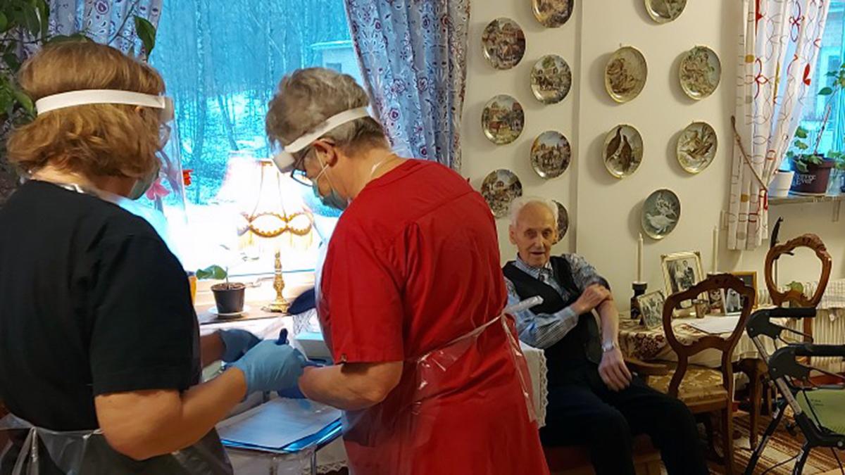 Två kvinnor i medicinska kläder och skyddsutrustning håller på att förbereda vaccin. Bakom dem sitter en man i 90-års åldern.
