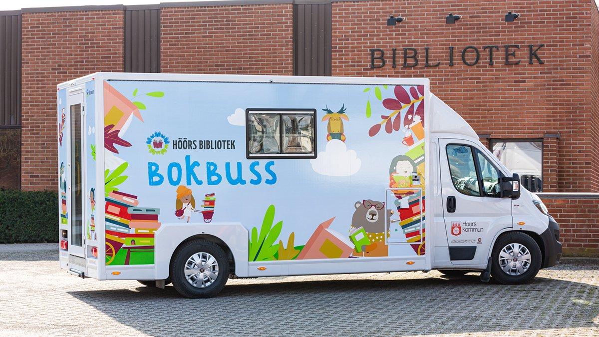 Bild på bokbussen, en vit minibuss med färgglada illustrationer på