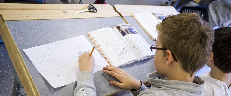 Pojke sitter i skolbänk och skriver