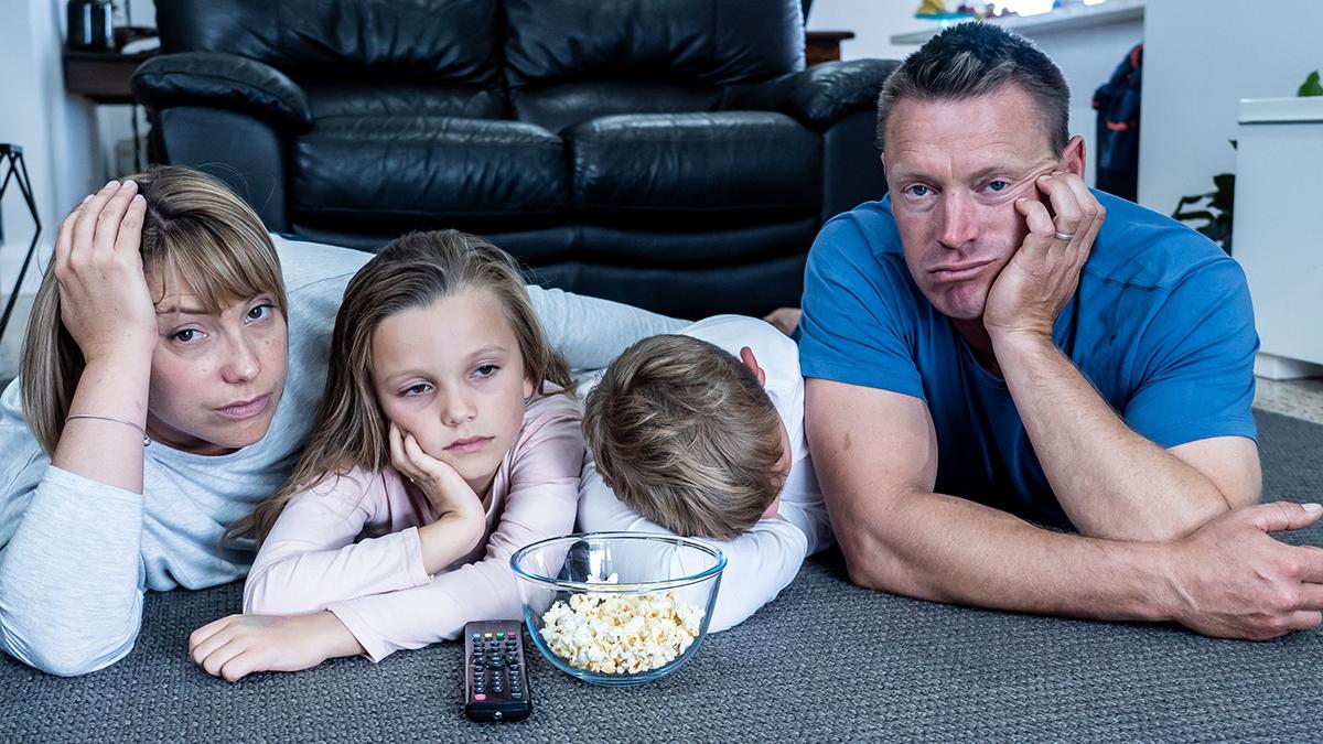 En familj på fyra personer halvligger på golvet och ser väldigt uttråkade ut.