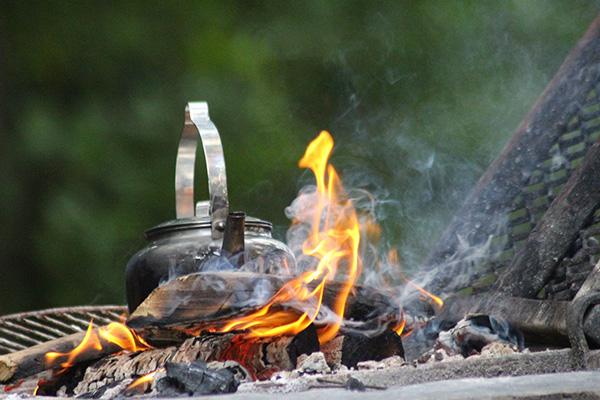 En kaffepanna på en öppen eld utomhus.