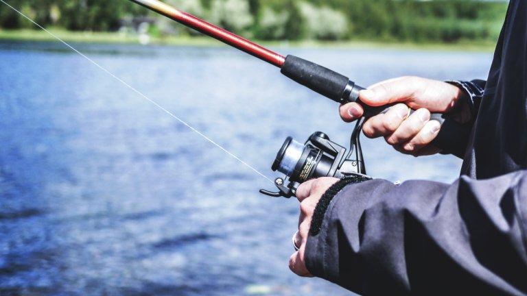 närbild av en fiskares händer och fiskespö med haspelrulle. I bakgrunden syns sjöns blåskimrande vatten.