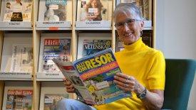 En äldre, kortklippt kvinna sitter och håller i tidningen Allt om resor. Hon har en gul polojumper på sig och ler in i kameran. I hyllan bakom henne syns rader med tidskrifter.