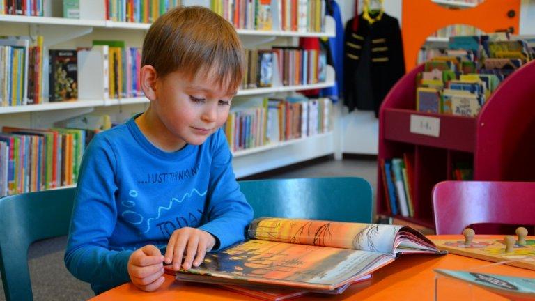 En 5-årig pojke sitter och bläddrar i en bilderbok på bibliotekets barnavdelning. Det är en färgglad miljö. Pojken har en blå tröja på sig. Det låga bordets färg är orange. De små stolarna är blå och lila.