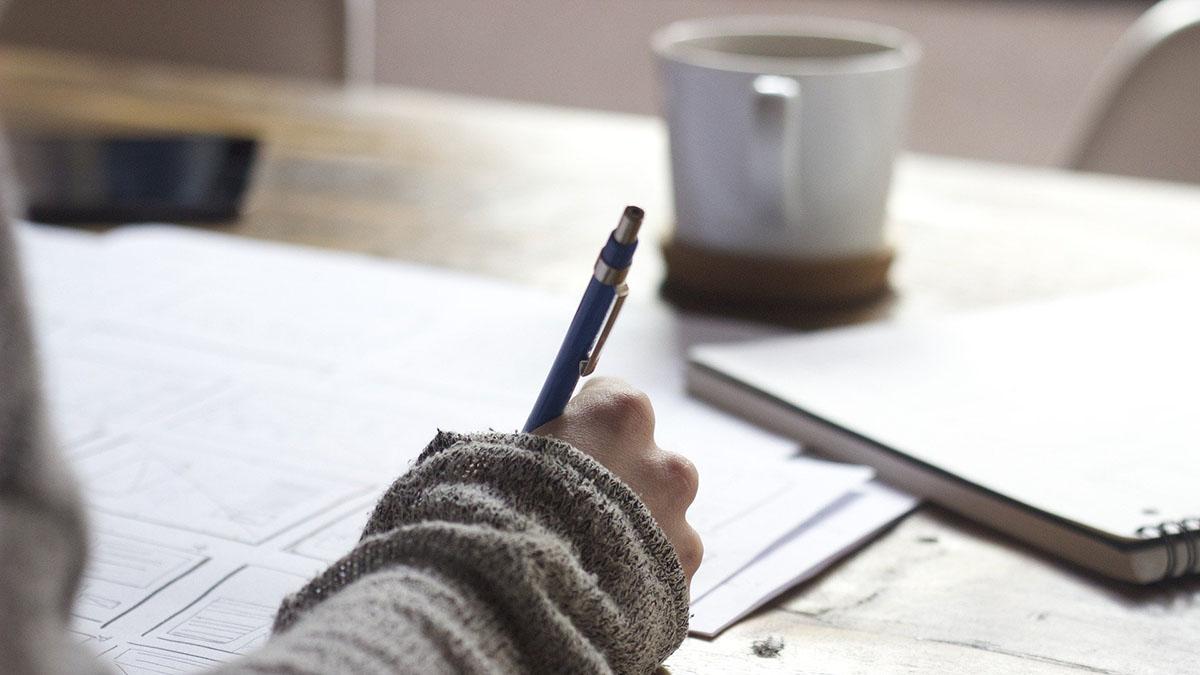En bild på en hand som som håller i en penna. I bakgrunden syns en kaffekopp.