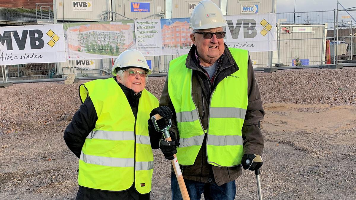 Två personer i reflexvästar med spade på byggplats för den nya boendet.