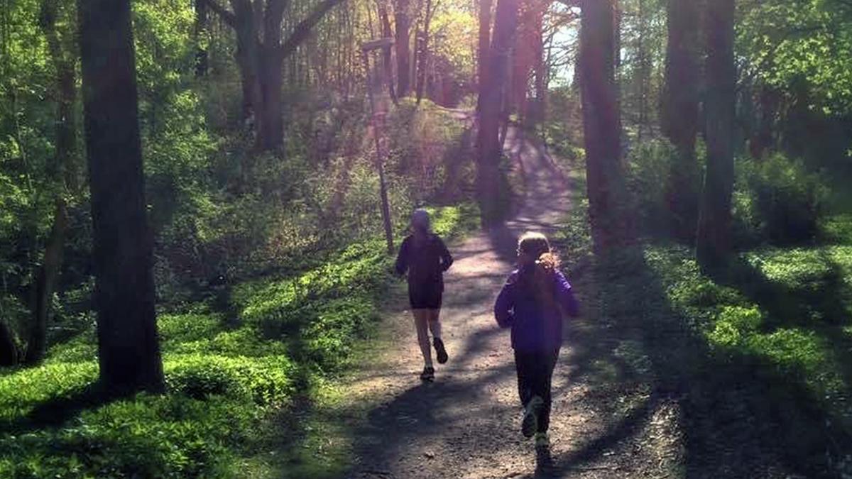 Två personer som springer på ett spår i skogen.