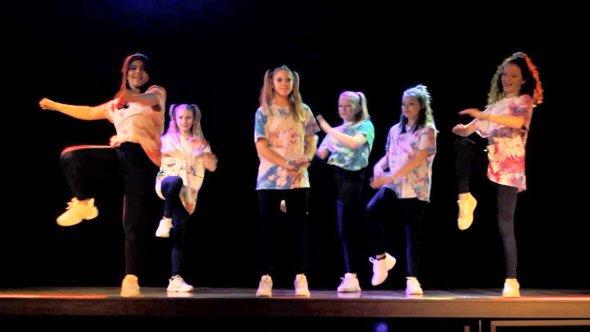 Sex ungdomar dansar på en scen.