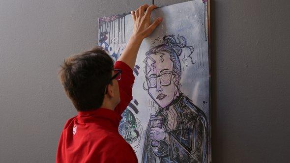 En person håller upp en tavla mot en vägg.